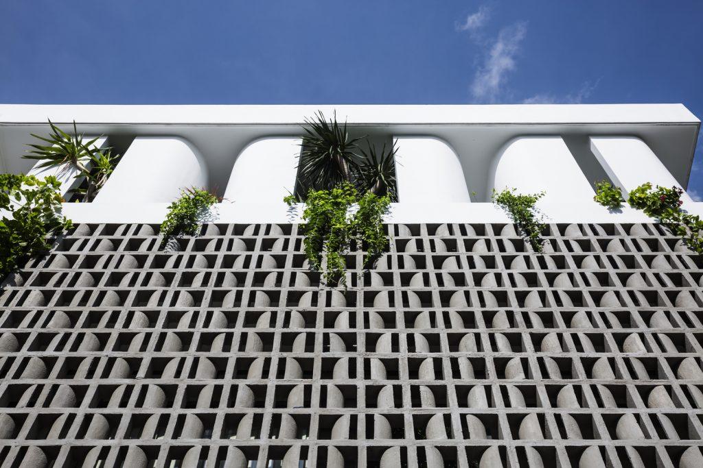 Cùng với khoảng tường lớn là gạch cong màu xám, bên trên mái nhà còn được thiết kế những khung tường cong màu trắng, tạo nên sự hài hòa.